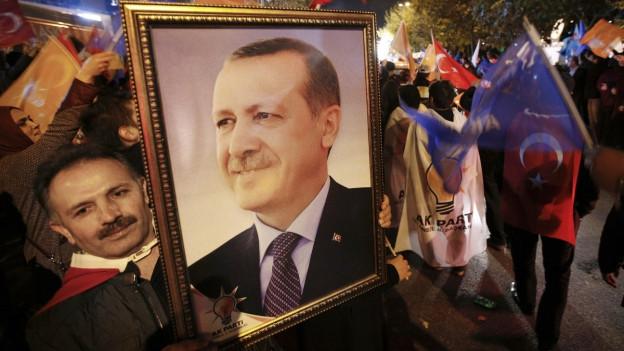 Ein Mann der die islamisch-konservativen AKP unterstützt, hält ein Porträt des türkischen Präsidenten Recep Tayyip Erdogan in den Händen