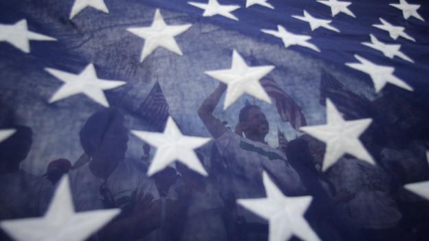 Menschen hinter einer US-Flagge.
