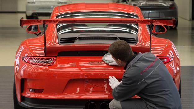 Ein Porsche-Angestellter kauert vor dem Heck eines roten Porsches.