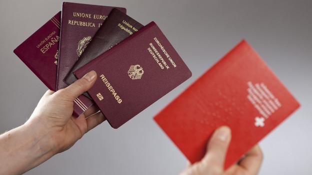 Zwei Hände, eine hält einen Schweizer Pass, eine andere verschiedene EU-Pässe.