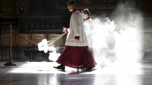 Das Bild zeigt zwei Messdiener, die Weihrauch verteilen im Petersdom.