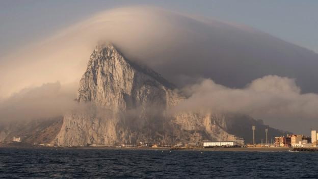 Der Felsen von Gibraltar vom Meer ausgesehen, von einer Nebeldecke bedeckt.