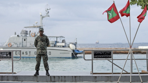 Ein Soldat steht Wache neben Flaggen der Malediven, wo für 30 Tage der Notstand gilt