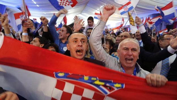 Auf dem Bild sieht man Anhänger der Konservativen HDZ. Sie jubeln und schwenken kroatische Fahnen