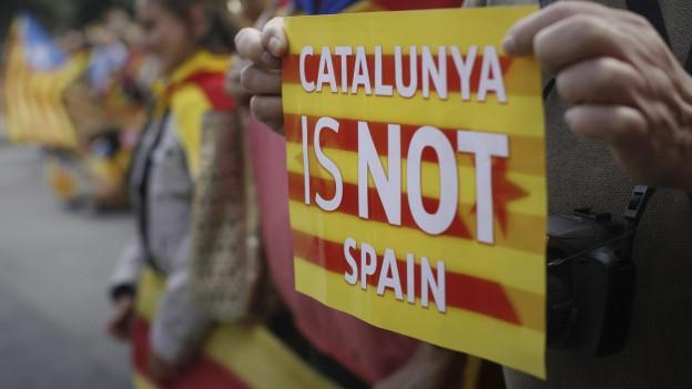 Demonstrant hält Schild in der Hand, mit der Aufschrift «Catalunya is not Spain».