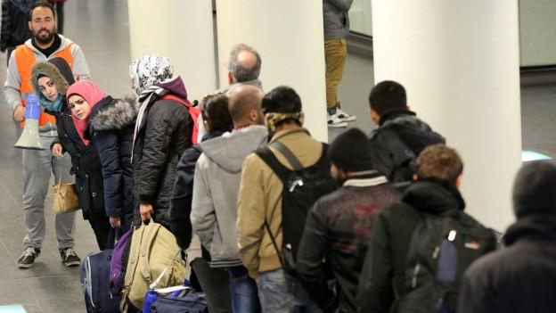 Asylsuchende warten in einer Schlange am Bahnhof in Rostock, um weiter nach Schweden zu reisen.