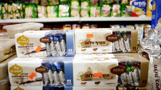 Biskuits, die in jüdischen Siedlungen hergestellt wurden, liegen aufgestapelt in einem Supermarkt.