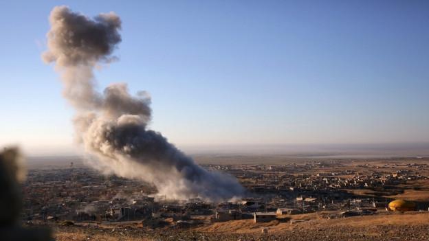 Rauch steigt auf über der nordirakischen Stadt Sinjar, wohl nach einem Luftangriff.