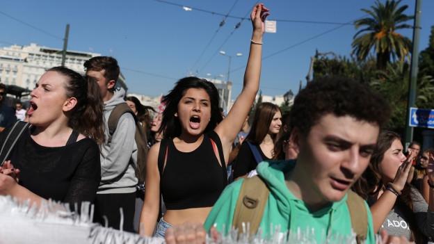Protestierende ziehen durch Athen, eine Frau hebt die Faust in die Luft.