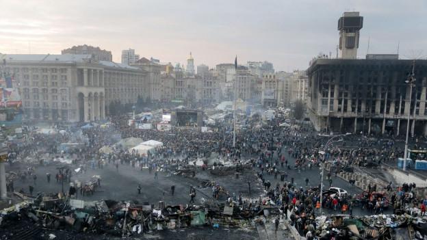 Totalaufnahme des Maidan-Platz in Kiew. Auf dem Platz demonstrieren Menschen gegen die damalige Regierung.