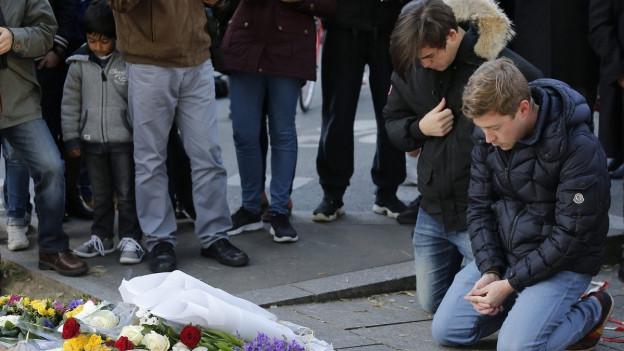 Zwei Männer knien nach den Terroranschlägen in Paris vor einem Blumenmeer in der Nähe der Konzerthalle Bataclan.