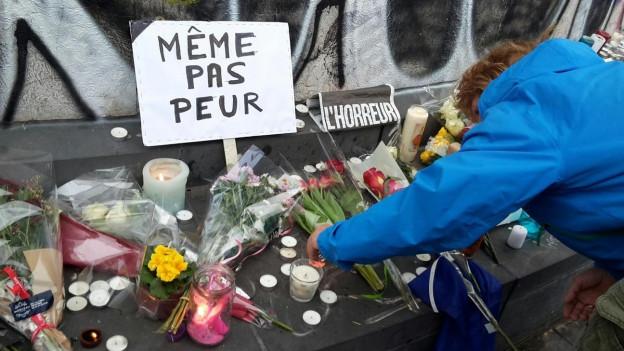 Eine Frau zündet in Paris eine Kerze an vor einem Schild «Même pas peur».