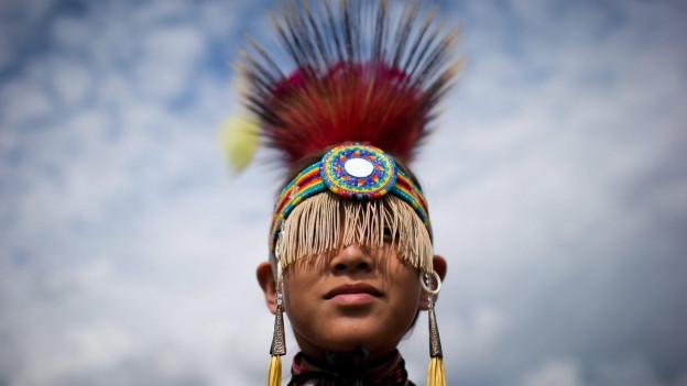 Angehöriger des Musqueam-Stammes mit farbigem Kopfschmuck.