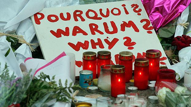 Viele Kerzen und ein Schild, auf dem steht: «Pourquoi? Warum? Why?