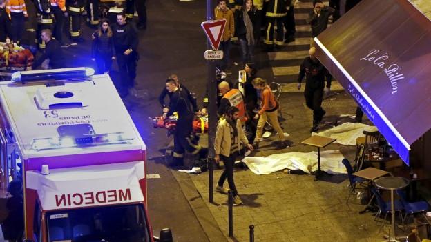 Die Aussenansicht eines Pariser Restaurants, davor steht ein Krankenauto mit blinkenden Blaulichtern.
