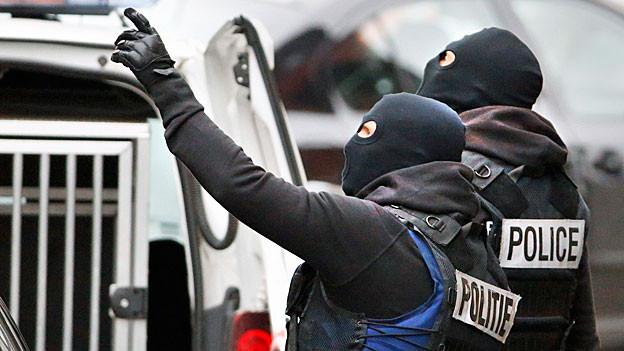 Zwei schwarz vermummte Polizisten beobachten ein Haus.