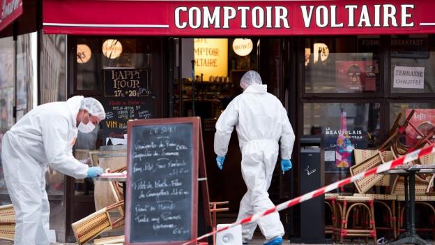 Das Bild zeigt Forensiker vor dem Café Voltaire in Paris.