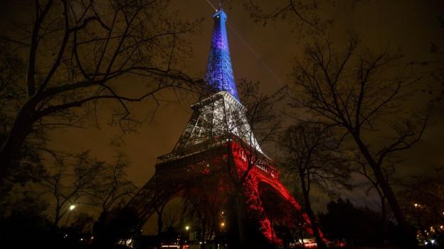 Der Eiffelturm - blau, weiss, rot beleuchtet, vor dunkelm Himmel.