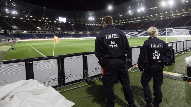 Zwei Polizeibeamte stehen im leeren Stadion in Hannover.