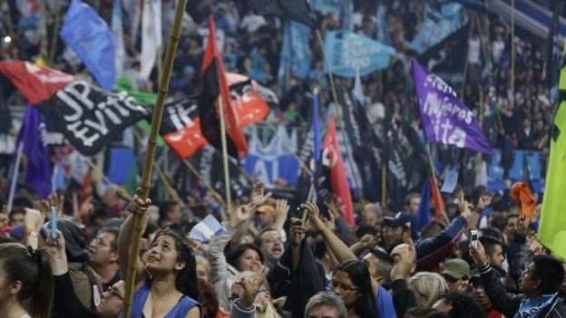 Anhänger von Scioli schwenken Transparente und Fahnen.
