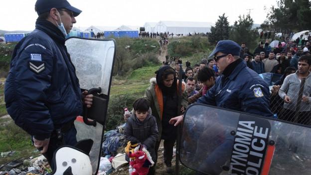 Zu sehen sind griechische Polizisten und Flüchtlinge an der Grenze zu Mazedonien.