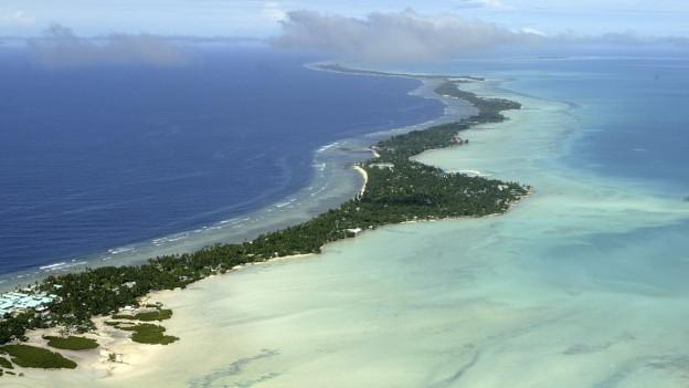 flache, lange, bewaldete Insel im türkisblauen Meer