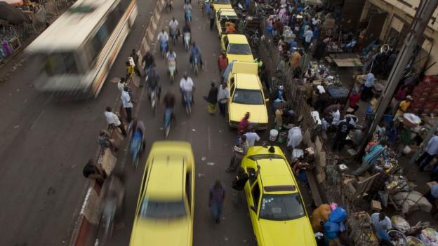 Strassenszene aus Bamako mit einer Menschenmenge und Autos.