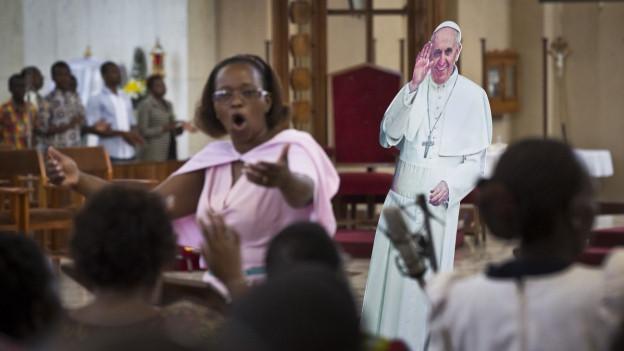 Ein Pappaufsteller des Papstes in einer Kirche in Nairobi, während davor der Chor singt.