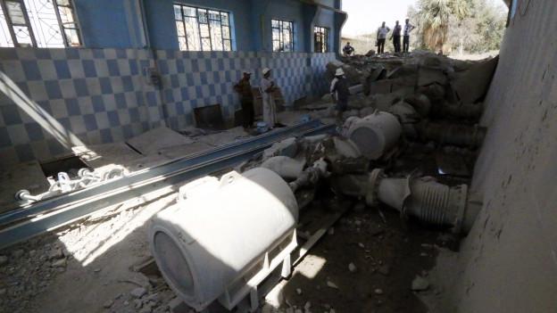 Männer inspizieren eine zerstörte Wasseranlage.