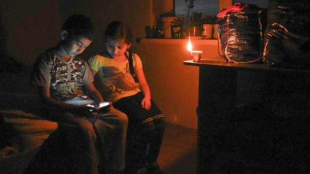 Kinder spielen auf der Krim bei Kerzenlicht mit dem Smartphone.