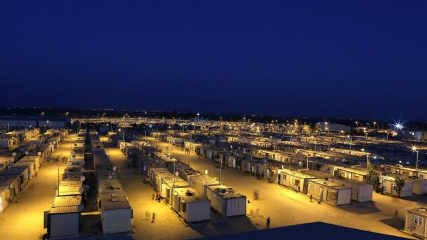 Flüchtlingslager bei Sanliurfa: Riesige Container-Siedlung nachts in gelbem Licht.