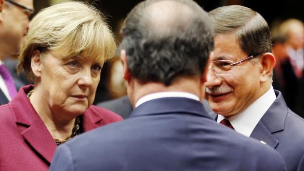 Die deutsche Bundeskanzlerin Angela Merkel und der türkische Ministerpräsident Ahmet Davutoglu, rechts sprechen mit dem französischen Präsidenten François Hollande