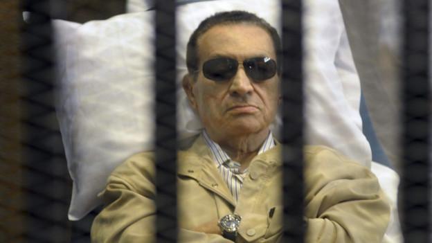 Mann mit Sonnenbrille in Krankenbett hinter Gitter.