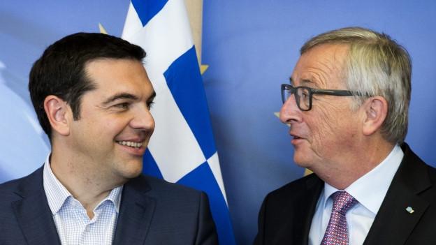 Auf dem Bild sind zwei lächelnde Politiker zu sehen: Links der griechische Regierungschef Alexis Tsipras, rechts der EU-Kommissionspräsident, Jean-Claude Juncker.
