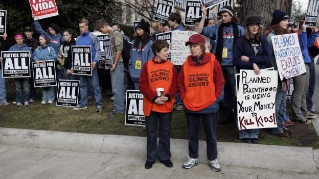 Vorne stehen zwei Frauen, die von einer Klinik von Planned Parenthood angestellt sind. Hinten steht eine Gruppe von Abtreibungsgegnern mit Plakaten.