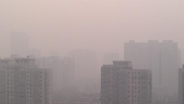 Hochhäuser in Peking verschwinden zum Teil wegen des Smogs.