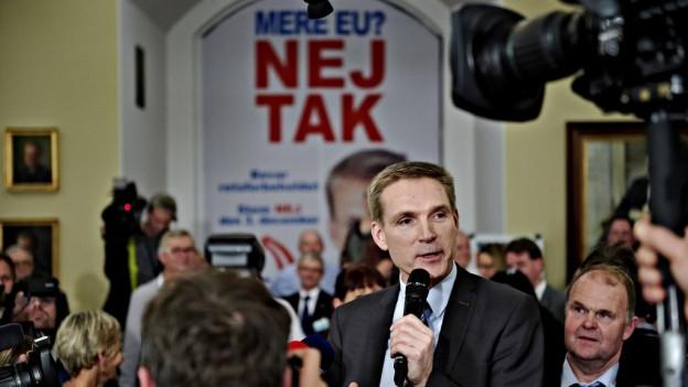Politiker mit Mikrofon, viele Leute, dahinter ein Plakat «Nej tak»