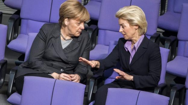 Bundeskanzlerin Angela Merkel und die deutsche Verteidigungsminister Ursula von der Leyen sprechen zusammen am 4. Dezember während einer Sitzung des deutschen Parlaments in Berlin.