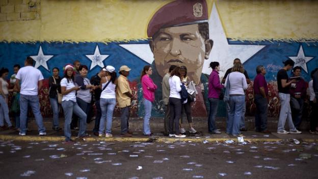 Wähler in Venezuela stehen vor einem Wahllokal Schlange. Dahinter ist ein Wandbild des verstorbenen Präsidenten Venezuelas, Hugo Chavez.