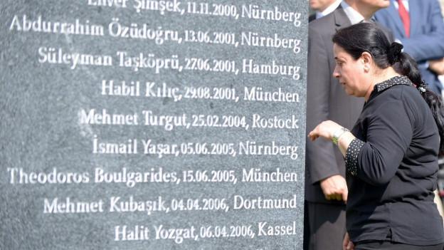 Die Witwe eines Opfers neben einer Gedenktafel für die NSU-Opfer.
