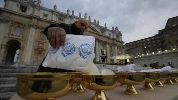Ein Vatikan-Angestellter füllt Kelche mit Hostien.