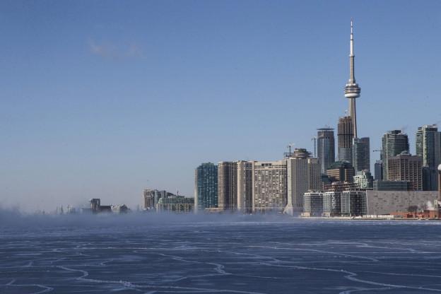 Die Skyline von Toronto mit den Wolkenkratzern und Türmen, davor das Meer.