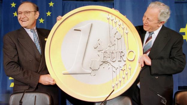 Das Bild zeigt eine Pressekonferenz der EU-Staats- und Finanzminister vom 1. Mai 1998. Zu sehen ist eine gigantische Euro-Münze.