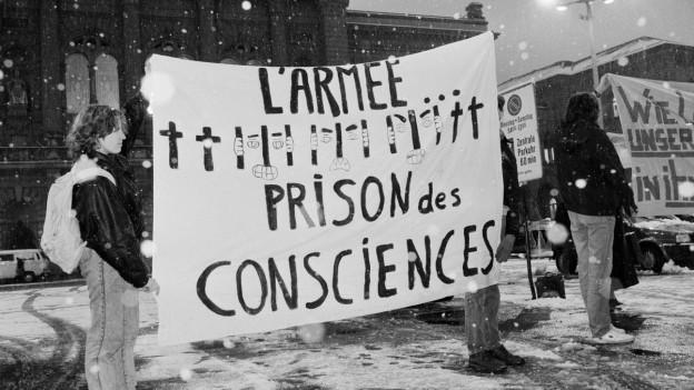 Das Bild zeigt Mitglieder des Initiativkomittees für eine Schweiz ohne Armee. Sie protestieren vor dem Bundeeshaus für die Abschaffung der Armee und die Entkriminalisierung von Dienstverweigerern.