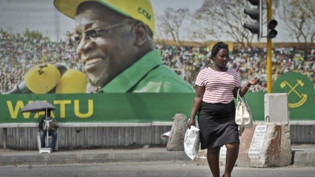 Eine tansanische Frau läuft über einen Platz, im Hintergrund sieht man ein Plakat mit dem Kopf von Präsident Magufuli.