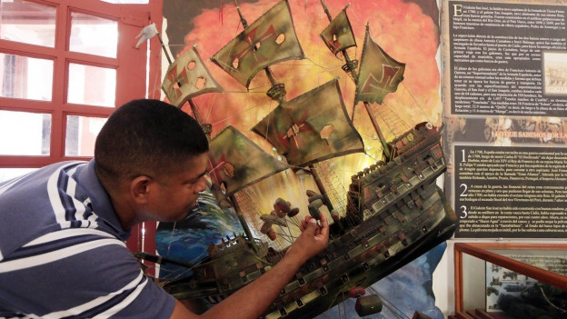 Mann hält Modell des spanischen Schiffs San José in den Händen.