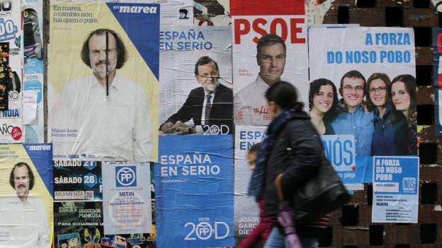 Eine Passantin läuft vorbei an einer Mauer mit Wahlplakaten.