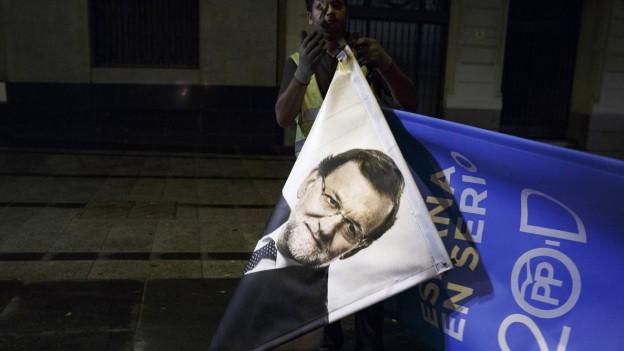 Ein Arbeiter entfernt in Madrid ein Wahlplakat des spanischen Ministerpräsidenten Mariano Rajoy.