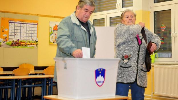 Auf dem Bild ist eine Schule in Sloweniens Hauptstadt Ljubljana zu sehen, wo ein älteres Ehepaar seine Stimme in eine Abstimmungsurne wirft.