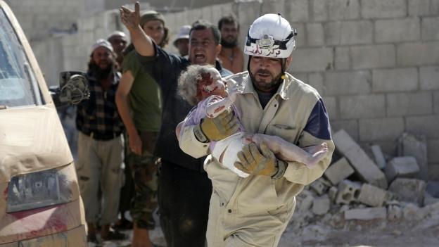 Das Bild zeigt einen Mann, der ein verletztes Kleinkind trägt. Im Hintergrund Trümmer.